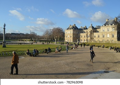 LUXEMBOURG GARDEN, PARIS/FRANCE - DECEMBER 2017: Landscape view of people walking around and taking sun bath during a sunny day of winter in Luxembourg garden. Luxembourg Palace behind, Paris/France.