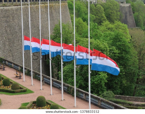 Luxembourg mourning for Grand Duke Jean: in the city national flags half mast, with black ribbons. Cloudy spring day.