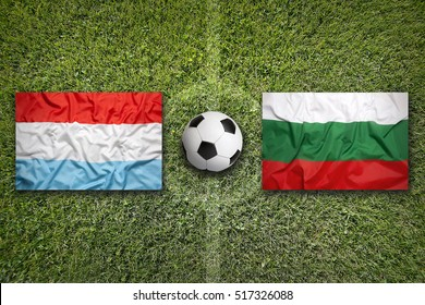 Luxembourg vs. Bulgaria flags on a green soccer field