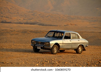 """LUXOR, EGYPT - 27 DECEMBER 2017: An old Peugeot 504 car parked in the Egyptian desert sands. Debuted as Peugeot's flagship in 1968, in 2013, the LA Times called the 504 """"Africa's workhorse."""" Editorial"""