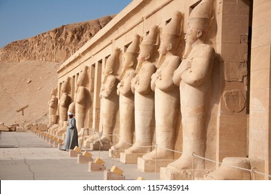 Luxor, Egypt, april 2018. Man in traditional egyptian dress walking along pharaoh statues at Hatshepsut temple