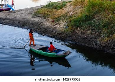 Luxor, Egypt - December 11, 2018: Two nubian boys in fishing boat on Nile river in Luxor, Egypt