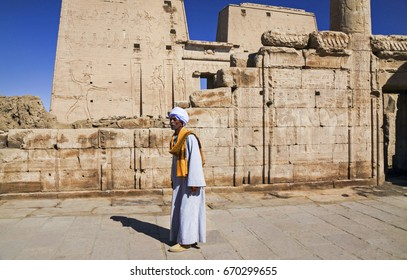 LUXOR, EGYPT - JANUARY 21, 2010: Local Old Man Person dressed in Traditional Nubian Clothing walking in ancient Egyptian Ruins in Temple of Philae near Valley of the Kings