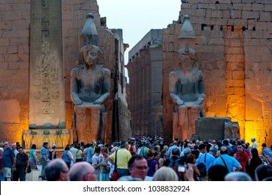 LUXOR, EGYPT - MARCH 16, 2010 : A crowd of tourists gather at the entrance pylon of the Luxor Temple (Temple of Amun-Ra). At the entrance stands the obelisk and two giant statues of Ramesses ll.
