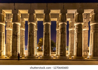 Luxor, Egypt - Nov 12th 2018 - A tourist having fun inside a huge temple at night at Luxor in Egypt