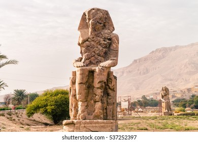 LUXOR, EGYPT - NOVEMBER 29, 2016: Ancient Colossi of Memnon in Egypt at noon. The original function of the Colossi was to stand guard at the entrance to Amenhotep's memorial temple.