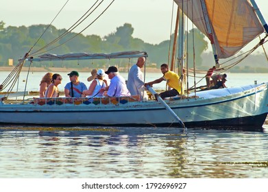 LUXOR, EGYPT - OCTOBER 16, 2011: Unidentified people on an excursion on the Nile River in felucca traditional wooden sailing boat. Young Egyptian leads the boat