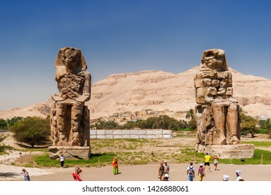 LUXOR, EGYPT - September 16, 2008. Tourists walking near Colossi of Memnon, massive stone statues of the Pharaoh Amenhotep III.