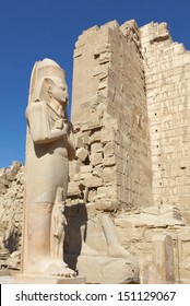 LUXOR, EGYPT-JUN 26:Majestic statue of Ramses II at feet in Hypostyle Hall of Karnak Temple, blue sky in the background. June 26, 2011. Luxor, Egypt.