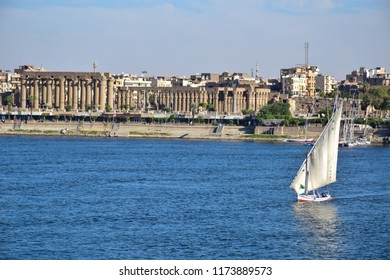Luxor/Egypt - 12/15/2016 - Sailing boat in the middle of the River Nile  and in the background Ancient pharaonic Luxor temple in Egypt