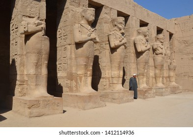 Luxor/Egypt_17 May 2019: The Karnak Temple Complex, commonly known as Karnak comprises a vast mix of decayed temples, chapels, pylons, and other buildings. An arabian man standing next to the statue.
