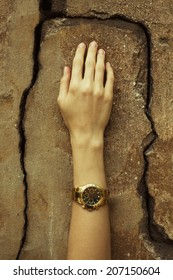 Luxurious accessory concept. Young woman's hand wearing a golden watch with golden strap over cracked stone wall. Perfect manicure. Vintage style. Close up. Outdoor shot