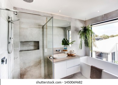 A luxurious bathroom with a bathtub and a shower with a glass division and planters to add style.
