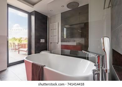 Luxurious bathroom with big bathtub and balcony door