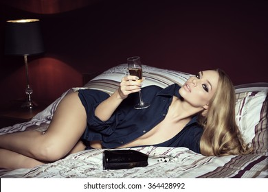 luxurious beautiful woman in erotic pose on bed with a glass and bottle of champagne, stylish make-up and open sexy shirt. Long blonde hair and freckles on visage