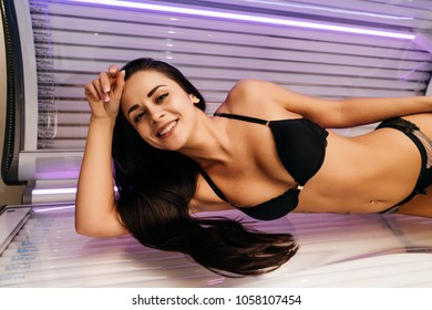 a luxurious beautiful young girl in a swimsuit lies in a horizontal sunroom and sunbathes, smiling