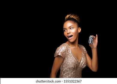 Luxurious Black Afro American Girl in a gold sequin dress with a perfect hairstyle and bright make-up is posing with casino chips in her hands. Casino, Poker and Roulette. Gambling dark-skinned Woman