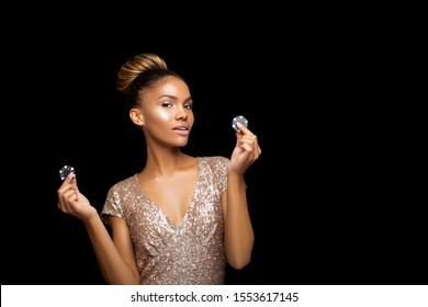 Luxurious Black Afro American Girl with a perfect hairstyle of picks and luxurious make-up is posing with black casino chips in her hands. Casino, Poker and Roulette. Gambling dark-skinned Woman Lucky