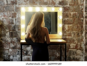 Luxurious brown hair girl undress long black dress . Elegant hairstyle cold wave. Background a mirror with bulbs. Lady stands with her back to the camera, showing a beautiful. rear view. naked back
