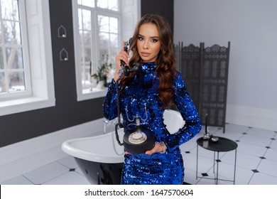 Luxurious brunette in blue dress with bright make-up and hairsty