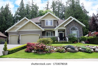 Luxurious Canadian mansion with a large professionally landscaped front yard.