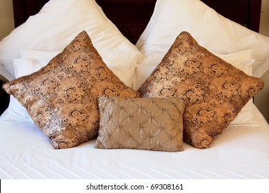 luxurious cushions on bed in gold brocade, silk and satin with white cotton linen