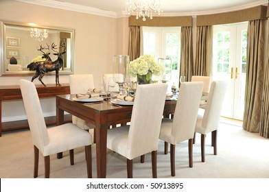 A luxurious dining room with table and chairs set for a meal