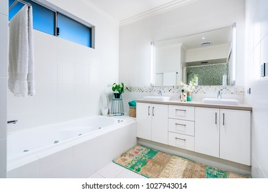 Luxurious and elegant bathroom interior with spacious bathtip and large mirror.