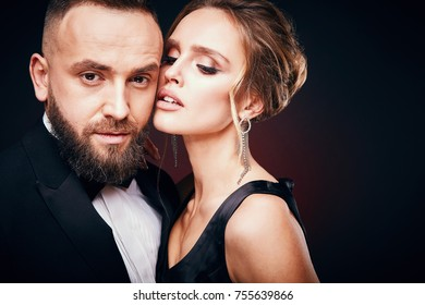 Luxurious, elegant couple: handsome bearded man in tuxedo with amazing woman with blonde updo hair, wearing silky black dress and chic jewelry, posing in dark studio