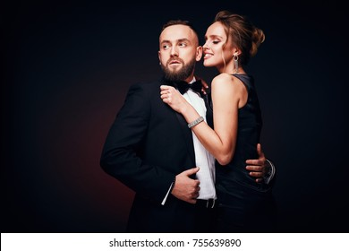 Luxurious, elegant couple: handsome bearded man in tuxedo with amazing woman with blonde updo hair in silky black dress and chic jewelry, posing in dark studio