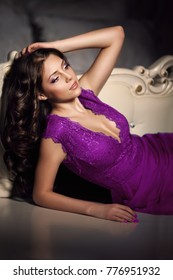 Luxurious female model in ultra violet dress. Beautiful stylish sexy girl