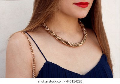 Luxurious gold necklace on girl with black shirt . Outdoor close up