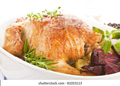 Luxurious grilled chicken with fresh herbs in baking dish prepared for eating.