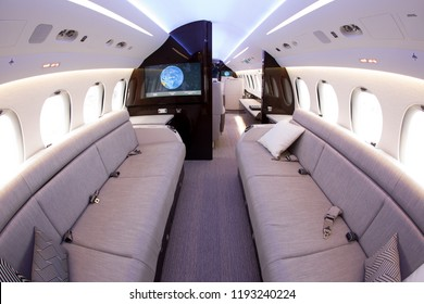 Luxurious interior of a business jet. Soft sofas, pillows, screens of on-board entertainment system.