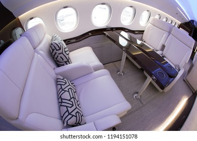 Luxurious interior of a business jet. Soft sofas, armchairs, pillows, and polished table.