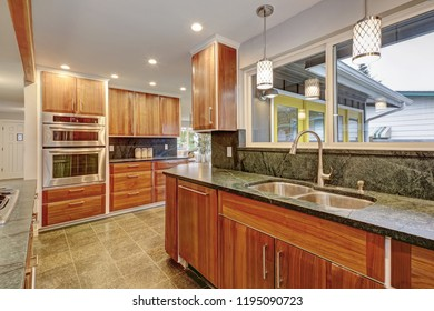 Luxurious kitchen room with wooden cabines and stainless steel appliances.