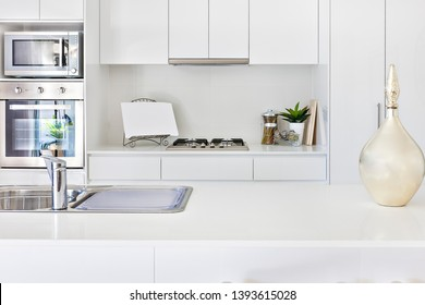 Luxurious Kitchen tools with white walls and oven, , evening time at kitchen, gas cooker also some glass bottles on pantry table, perfect lightning.