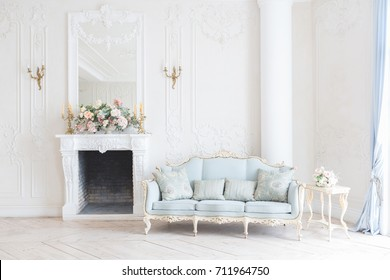 luxurious light interior in the Baroque style. A spacious room with a road chic beautiful furniture, a fireplace and flowers. plant stucco on the walls