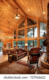 A luxurious living room, with comfortable furnishings, in a modern log cabin in the mountains.