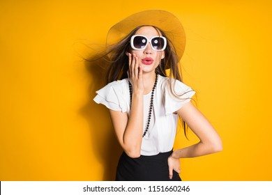 luxurious long-haired girl in a fashionable hat and sunglasses posing on a yellow background