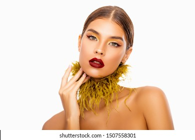 Luxurious Makeup. Art Make-up. Beautiful Fashion Portrait woman with Style golden Make up on the eyelids and Red Lips. Red eyeliner. Gold feathers on the neck.