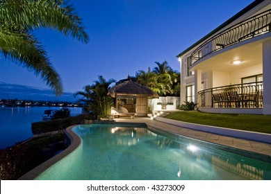 Luxurious mansion exterior at dusk overlooking pool, canal and Bali hut