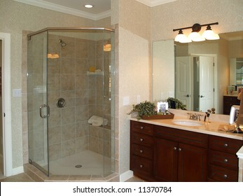 Luxurious marble bathroom with glass enclosed shower and dark wood vanity