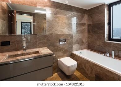 Luxurious marble bathroom with window. Nobody inside