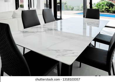 Luxurious marble dining table with black chairs.
