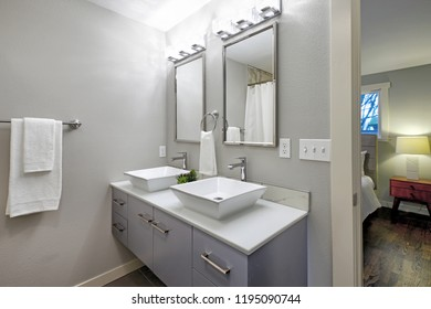 Luxurious master bathroom with blue vanity cabinet and two square vessel sinks.