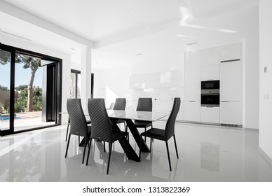 Luxurious modern dining room with white table, black chairs and white modern kitchen.  Minimalistic style.