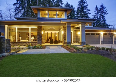 Luxurious new construction home exterior with front patio and column porch. Outdoor living space boasts taupe wicker chairs facing a stone outdoor fireplace. Northwest, USA