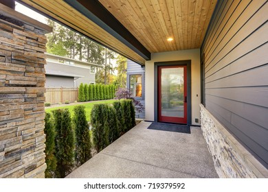Luxurious new home with long covered porch features plank ceiling, stone column and concrete floor. Northwest, USA