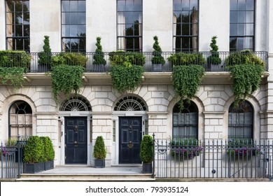 Luxurious old apartament house with a white facade and green plants, London, UK